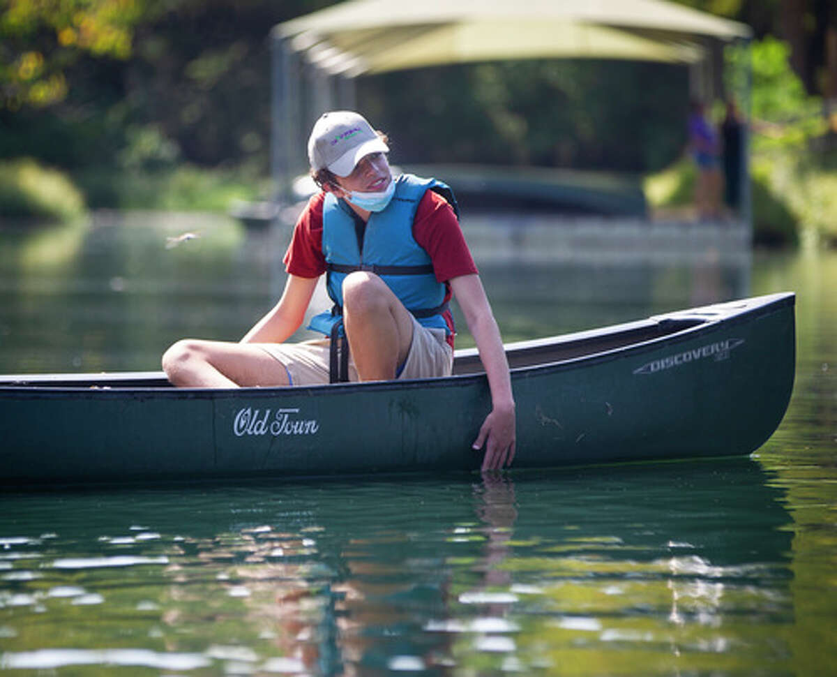 Paul Perez dips his hand into the water as he canoes with his mother, Suzanne Garofalo, at Camp for All, Saturday, Oct. 10, 2020, in Burton, TX.