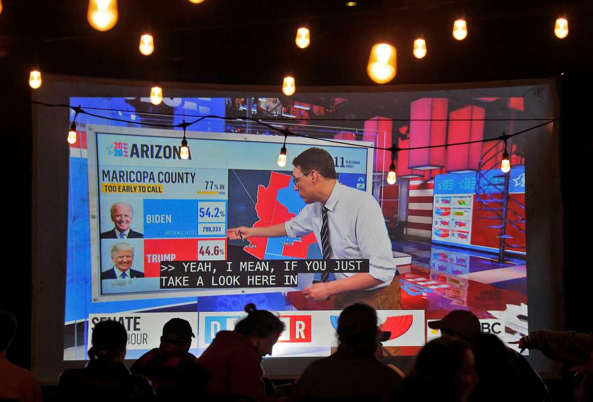 Results for Arizona are projected on a screen as guests watch during an election watch part at 7th West Bar in Oakland, Calif., on Tuesday, November 3, 2020.