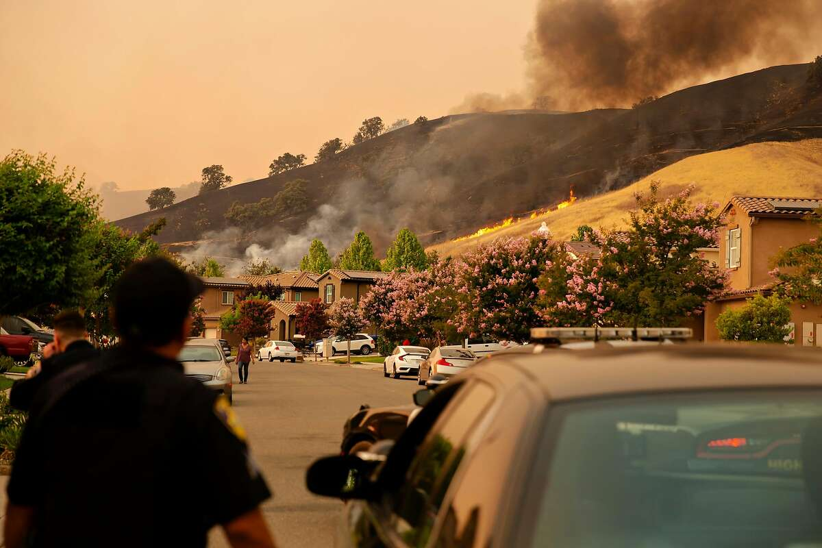 Flames from the LNU Lightning Complex burn across the hills behind homes in Fairfield in August. The state has told insurance companies that they cannot refuse to renew coverage in wildfire areas.