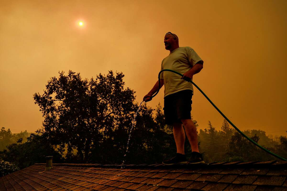 Tim Plowman waters down a friend's home as he tries to save it from impending fire before evacuating due to the LNU Lightning Complex Fire in Vacaville in August.