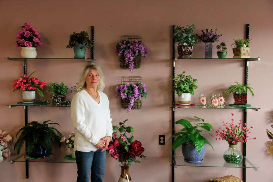 Sue Backes poses with some of her artificial plants inside the Forever Yours store. Backes works in making arrangements for artificial plants along with plant hangers and other crafts. (Robert Creenan/Huron Daily Tribune)
