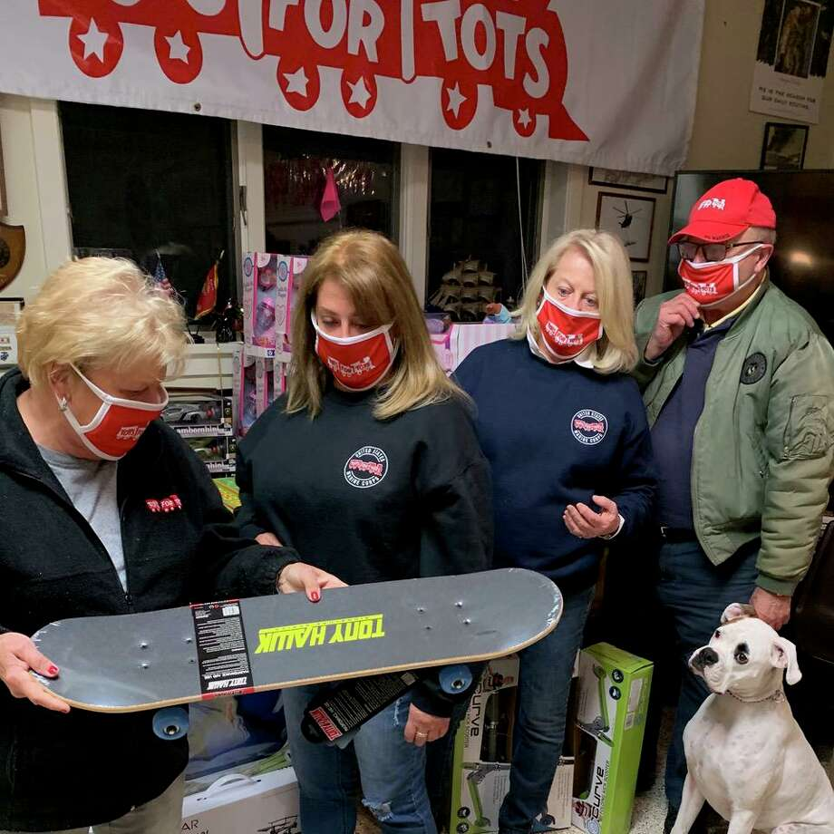 Toys for Tots coordinators (from left) Shirley Wilken and Pam Petti along with campaign program co-chairs Carole Watson and Henry Norley check out a skateboard with advice from United States Marine Corp Canine 1st Sgt. Oliver Norley during a previous Toys for Tots campaign program, which has just started for this year, 2020. The Toys for Tots program, which serves disadvantaged children at Christmas time, distributes more than 30,000 unwrapped toys and sports items every year with the help of local churches and youth organizations. It is operated by the Marine Veterans of Fairfield County. Norley is also a longtime member of the Marine organization and a coordinator of the Toys for Tots campaign program. Photo: Marine Veterans Of Fairfield County / Contributed Photo
