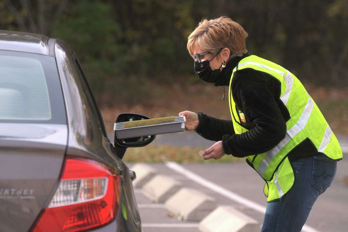 Leslie Hammer assists a voter with her curbside voting needs on Tuesday outside of Ludlowe High School in Fairfield.