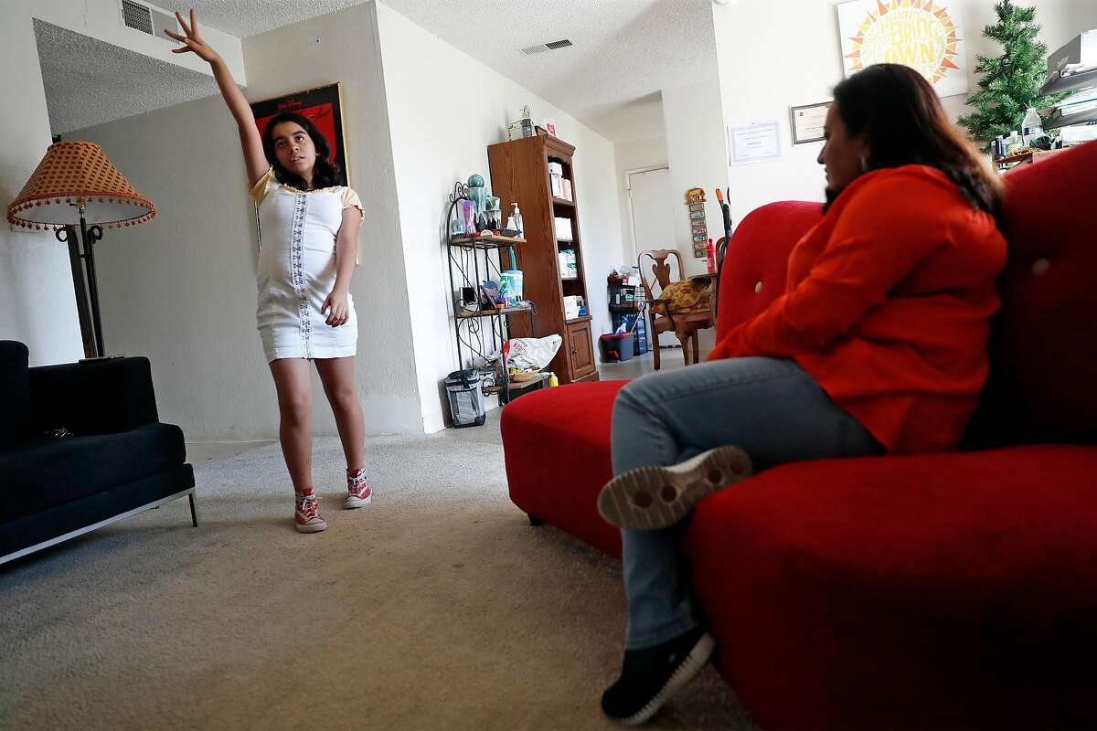 Aleida Ramirez watches her daughter, Emily, 11, dance at their apartment at Clayton Crossing Apartments , Calif., on Monday, November 2, 2020. Ramirez has joined other tenants in fighting a rent increase and poor living conditions.