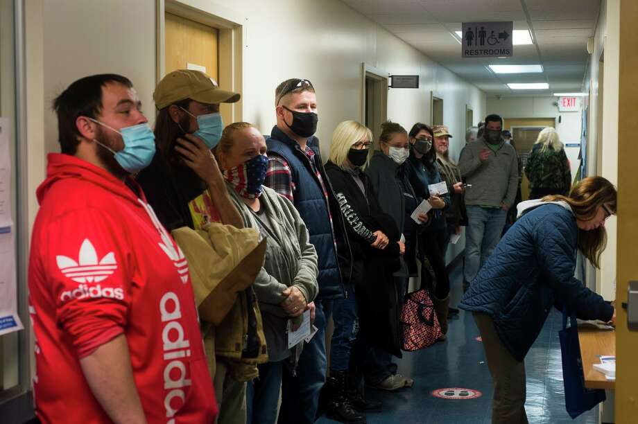 Voters wait in a long line to cast their ballots at the Jerome Township Hall Tuesday, Nov. 3, 2020 in Sanford. (Katy Kildee/kkildee@mdn.net)