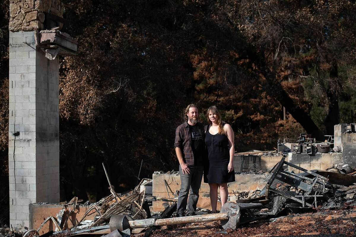 Jon Payne and his wife Elizabeth pose in front of the remains of their house in the Santa Cruz mountains. The Paynes had just finished work on a home recording studio when the CZU Lightning Complex Fire swept through and destroyed the house.