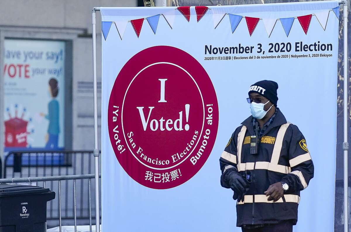 In this Oct. 20 file photo, a security guard stands near an exit at a San Francisco Department of Elections voting center near City Hall.