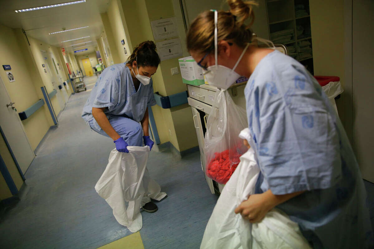 Nurses put on protective suits before doing a round tending to COVID-19 patients in negative pressure rooms. The CEO of Jacksonville's Passavant Area Hospital said Thursday that he is increasingly concerned about a strong surge of cases in west-central Illinois.