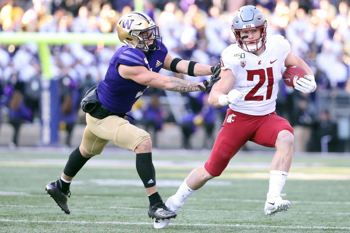 SEATTLE, WASHINGTON - NOVEMBER 29: Max Borghi #21 of the Washington State Cougars is pushed out of bounds by Elijah Molden #3 of the Washington Huskies in the first quarter during their game at Husky Stadium on November 29, 2019 in Seattle, Washington. (Photo by Abbie Parr/Getty Images)