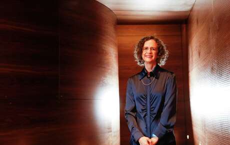 Deborah Brochstein stands in the MFAH Kinder Building's Lynn Wyatt Theater, where her woodworking company's American black walnut lines the walls.
