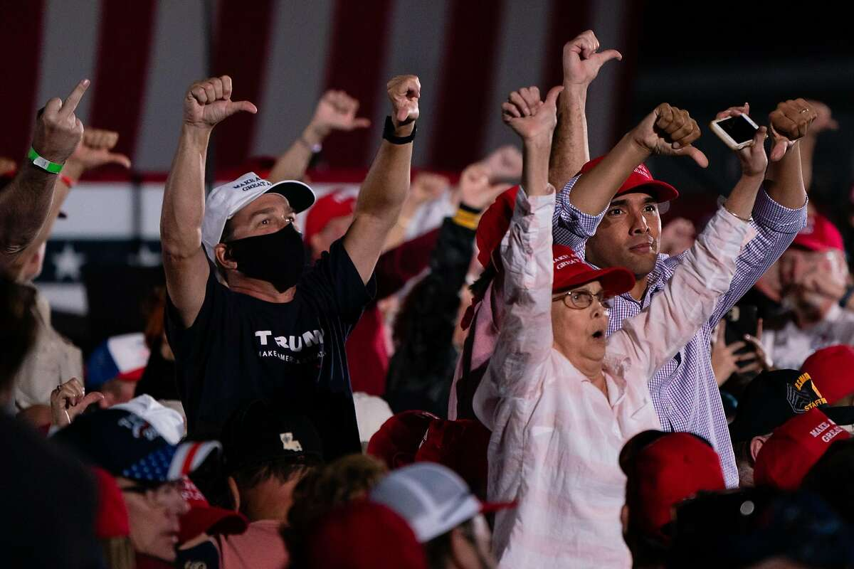 President Trump's supporters gesture at reporters during a rally in Macon, Ga.