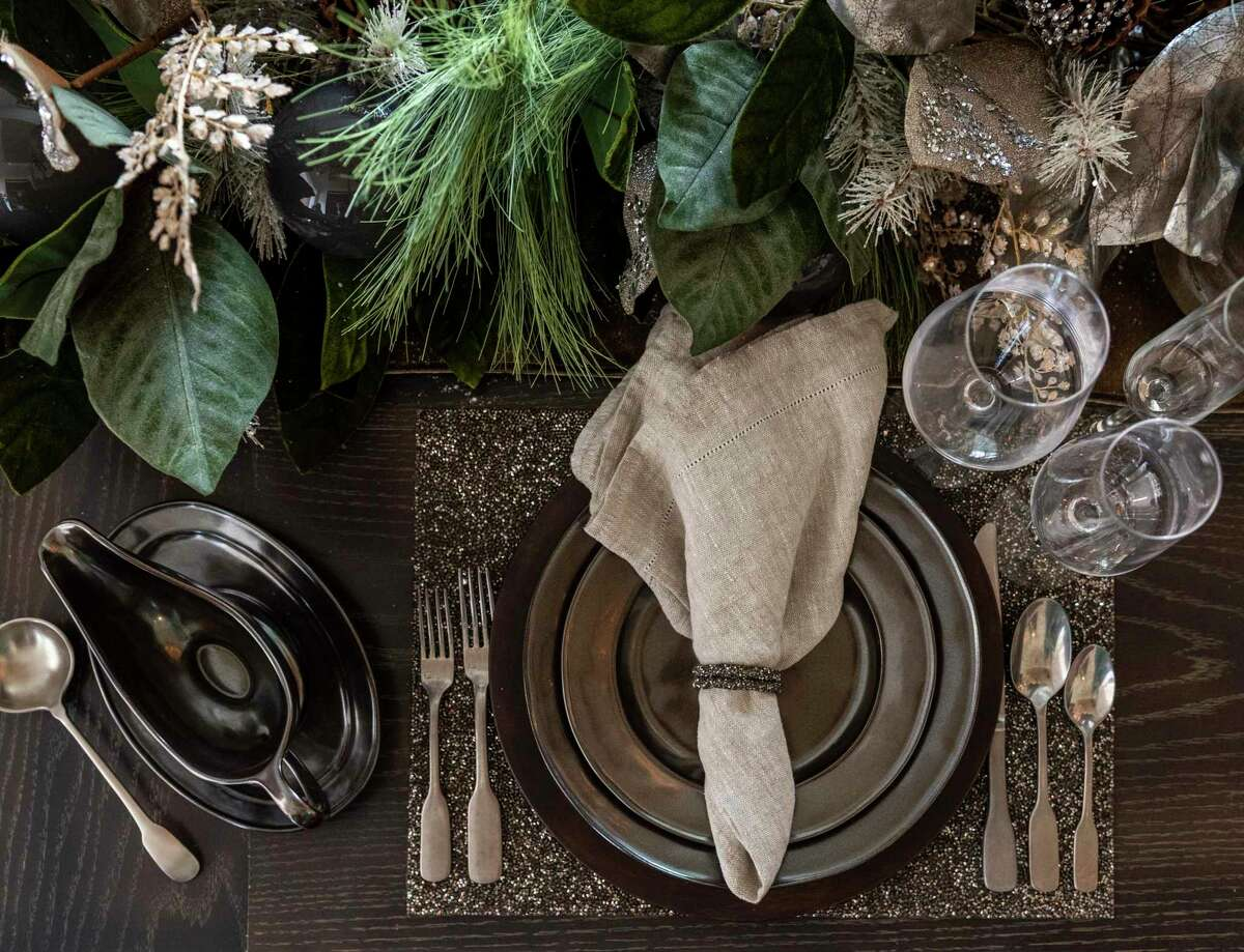 Sisters Regina and Janet Gust designed a holiday table that you can use as a base and then swap out ornaments, flowers and other decor to adjust to your holiday or dinner party. In this one -- the base decor -- they used dark Juliska dishes with Simon Pearce and Tritan crystal stemware. the centerpiece is lush evergreen with magnolia leaves, glittery gold fronds and a combination of clear and irridescent glass balls. They used faux -- to show how fabulous it can be -- but you could use fresh foliage, too.