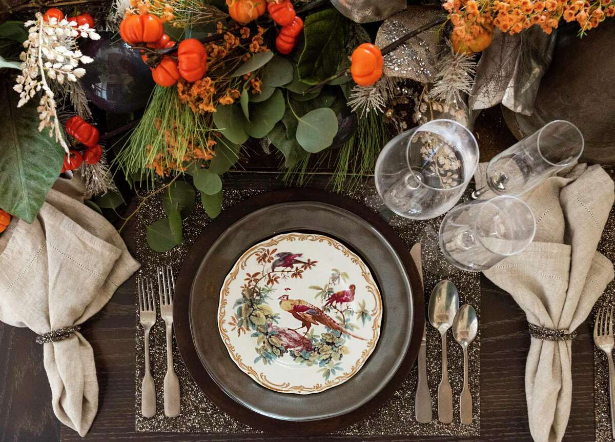 Adding mini pumpkins and orange flowers to the garland, and porcelain plates with pheasants brings a fall flair to the table decor for Thanksgiving.