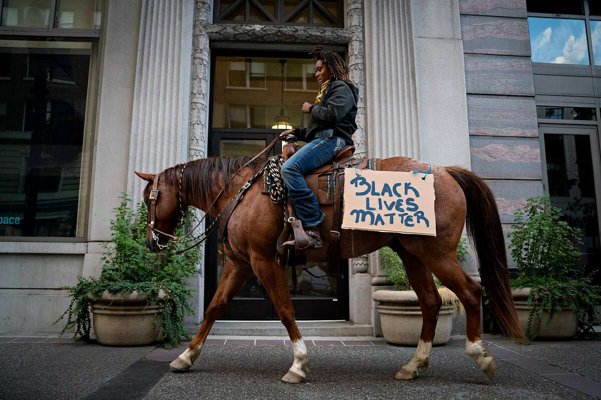 """Brianna Noble, 25, rides her horse named Dapper Dan, through the streets of downtown Oakland at the start of a protest honoring George Floyd on Friday, May 29, 2020 in Oakland. """"There is no image bigger than a black woman on a large horse,"""" said Noble. """"This is the image we would like to see portrayed in our community."""""""