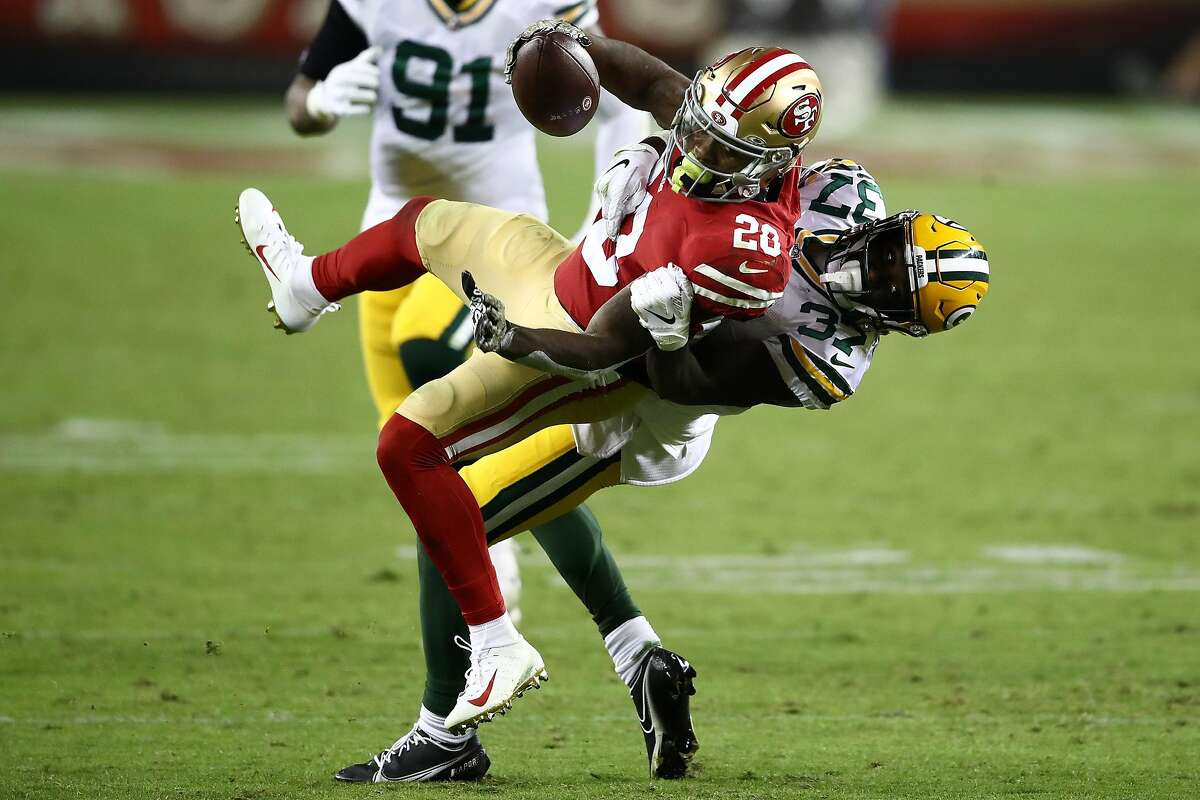Jerick McKinnon #28 of the San Francisco 49ers is tackled by Josh Jackson #37 of the Green Bay Packers during the third quarter at Levi's Stadium on November 05, 2020 in Santa Clara, California.