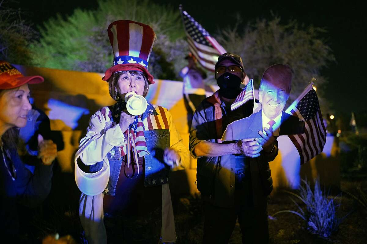 Supporters of President Donald Trump protest the Nevada vote in front of the Clark County Election Department, Thursday, Nov. 5, 2020, in Las Vegas. (AP Photo/John Locher)