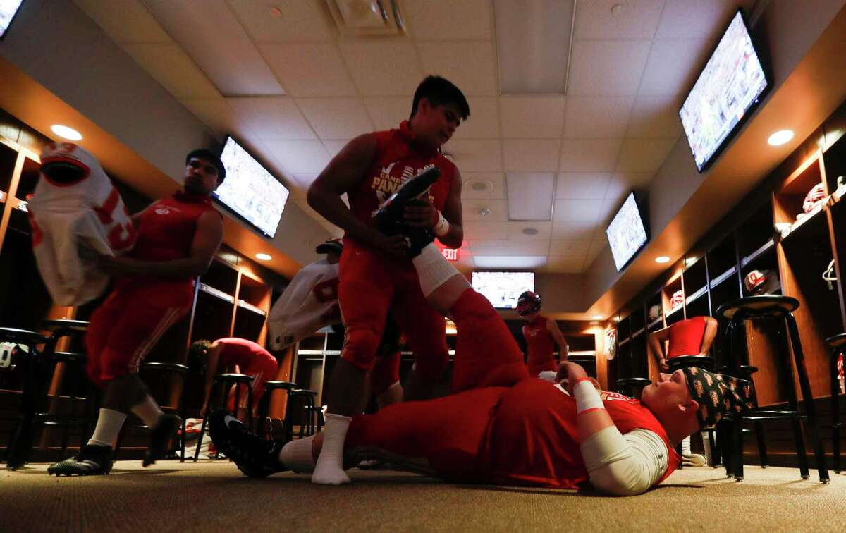 Caney Creek offensive linemen Christian Slabic (60) helps stretch defensive linemen Nathan Lucas (79) before a District 8-5A high school football game at Randall Reed Stadium, Thursday, Nov. 5, 2020, in New Caney.