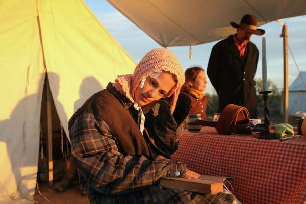 Pecos Hopkins, 11, sits down to read a novel as she camps with family at Horse Head Crossing in Pecos County on Oct. 31, 2020. They are volunteers with the Fort Griffin Living History Association.