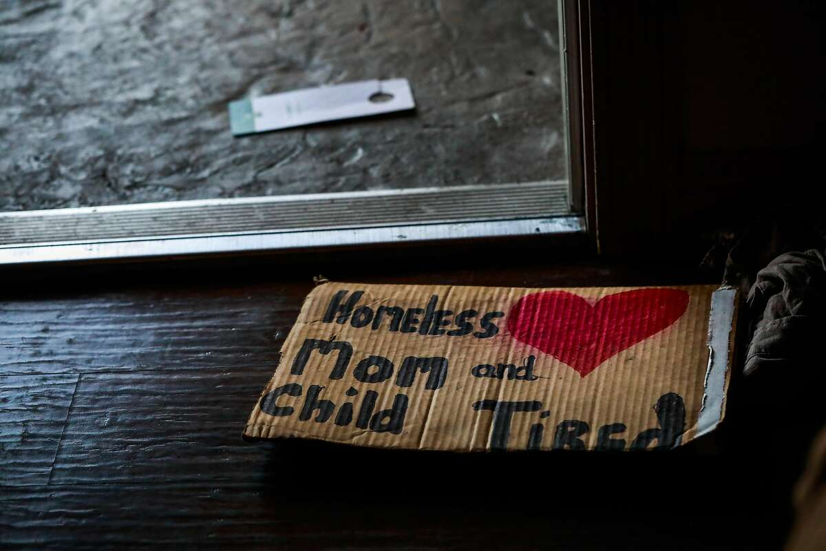 """A handmade cardboard sign stating """"Homeless Mom and Child Tired"""" sits on the floor of Leah Naomi Gonzales and her son Theo Schrager's, 6 hotel room at the Quality Inn after Leah panhandled under the freeway in Berkeley, California, on Sunday, Aug. 25, 2019."""