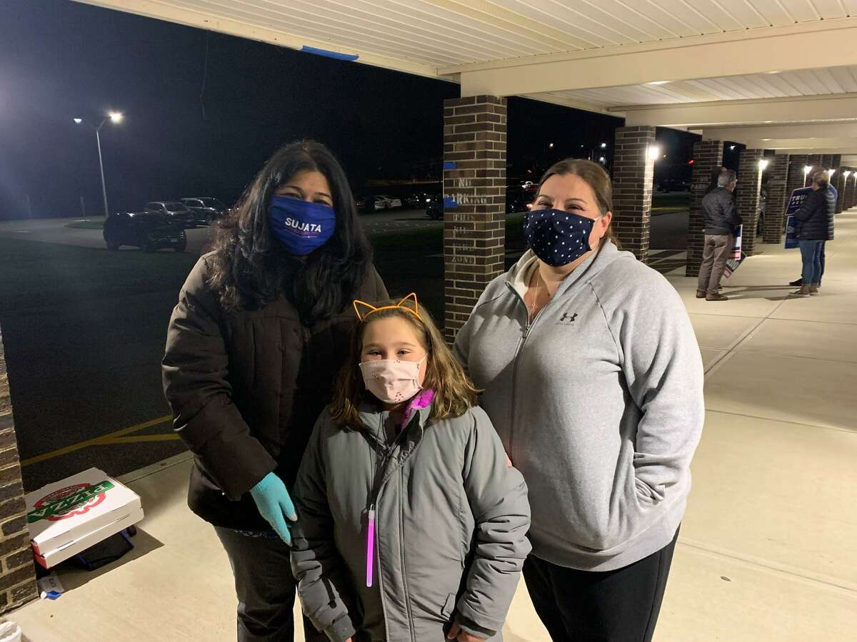 Sujata Gadkar-Wilcox greets Grace (center) and Sylvia Kapica shortly before polls closed at Hillcrest Middle School. Grace put in a full day selling Girl Scout cookies outside the school.