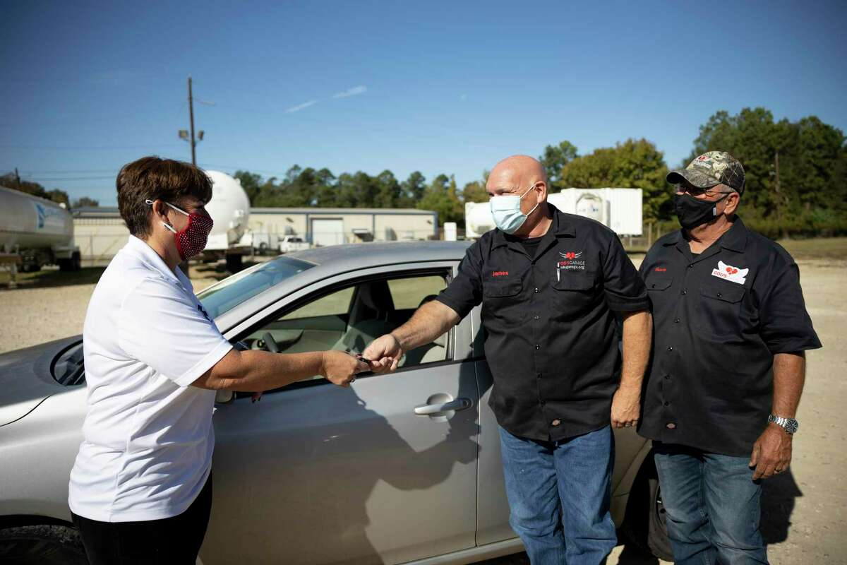 Desi Bittner hands the keys of her 2010 Toyota Corolla to James Minteer and Harvey Yaw of God's Garage in Conroe, Thursday, Nov. 5, 2020. The mission of the organization is to help single mothers, widows and wives of deployed military with a new vehicle they've fixed.