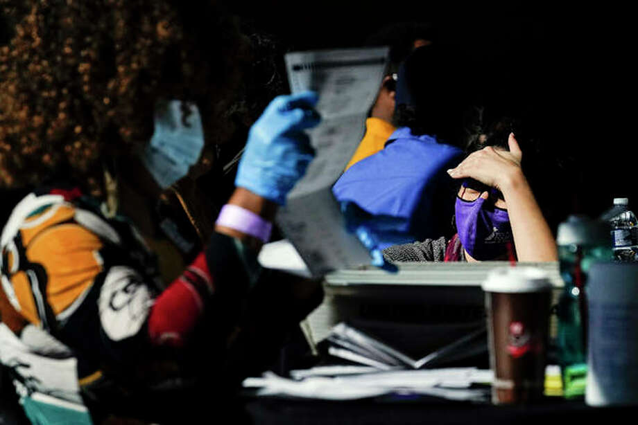 An election supervisor answer questions from an election worker as vote counting in the general election continues at State Farm Arena on Thursday, Nov. 5, 2020, in Atlanta. Photo: AP Photo/Brynn Anderson