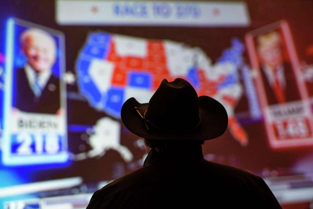 A supporter of Republican congressman Dan Crenshaw watches election returns on a television during an election watch party Tuesday, Nov. 3, 2020 in Houston.