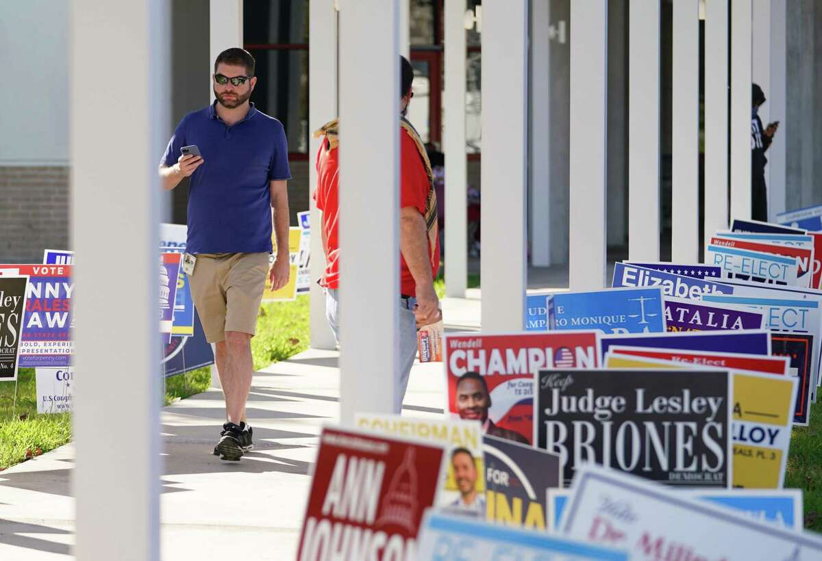 People walk by campaign signs at the Metropolitan Multi-Services Center, 1475 West Gray St., on Election Day Tuesday, Nov. 3, 2020 in Houston.