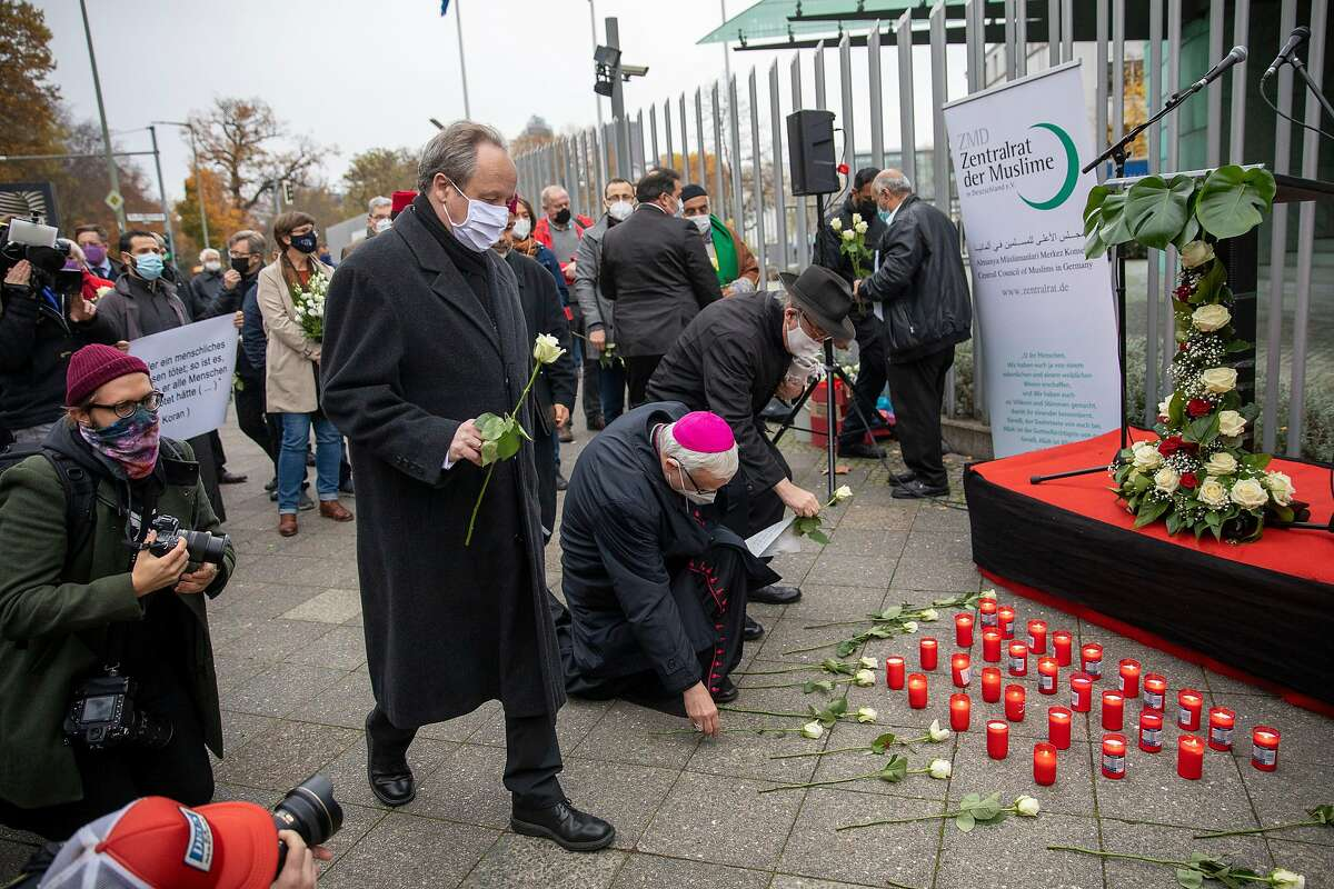 People place flowers outside the Austrian Embassy in Berlin in memory of the victims of Monday's terror attack in Vienna.