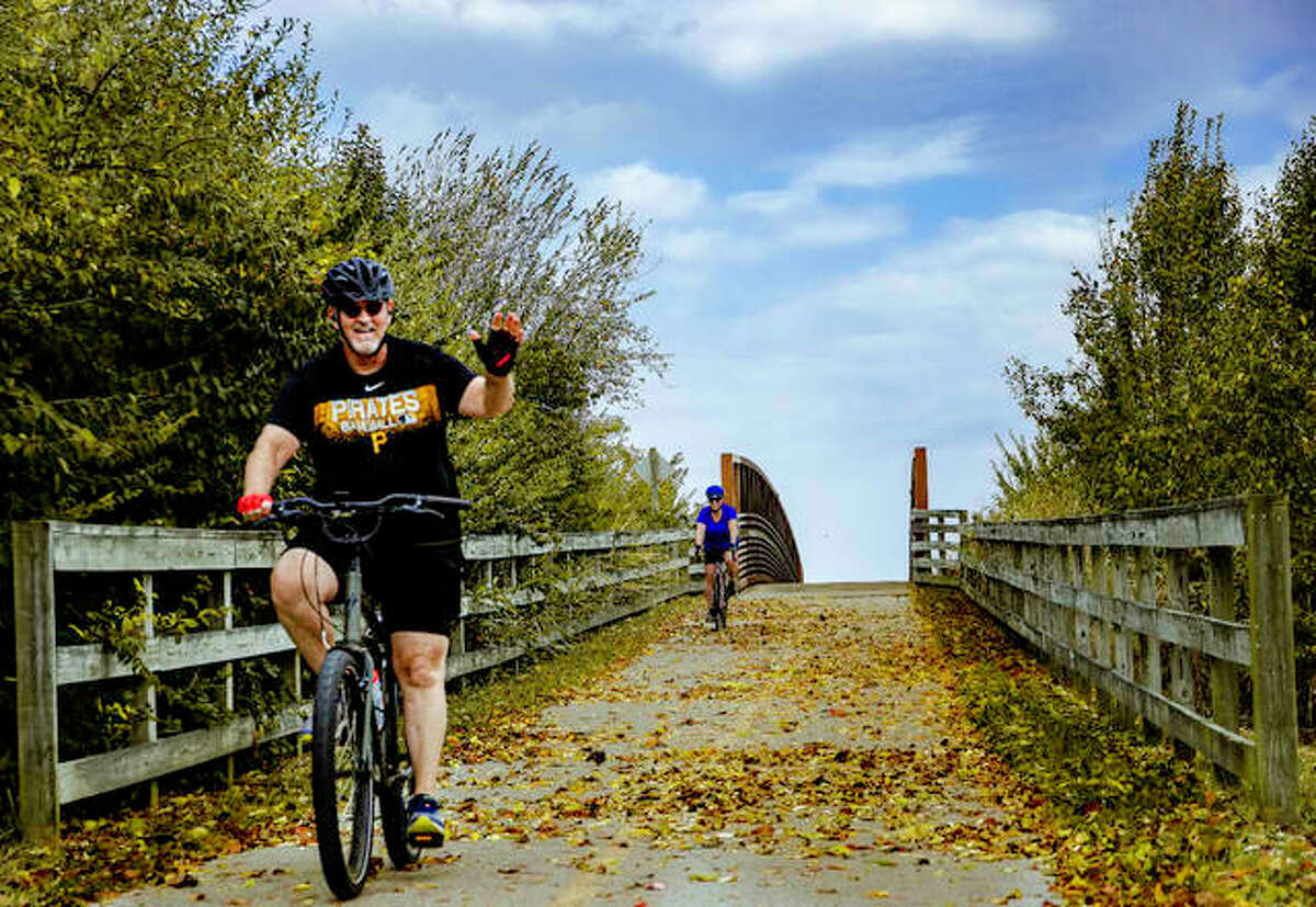 A cyclist waves as he and his partner take to the MCT trail and cross Illinois 162 near Old Troy Road in Marvyville on Oct. 12.