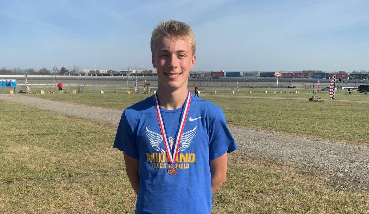 Midland High's Matthew Crowley displays his medal after finishing 17th in the Division 1 cross country state final Friday, Nov. 6, 2020, at Michigan International Speedway in Brooklyn.