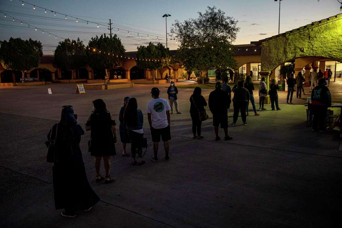 Voters wait in line at dawn for a polling place to open in Guadalupe, Ariz., on Election Day.