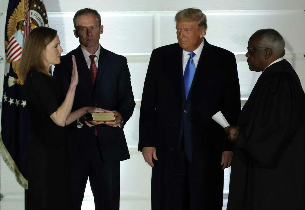 Donald Trump, second from right, watches as Supreme Court Associate Justice Amy Coney Barrett is sworn in by Supreme Court Associate Justice Clarence Thomas, right, as her husband Jesse Barrett holds a bible during a ceremonial swearing-in event on the South Lawn of the White House Oct. 26. Six of the nine Supreme Court justices were chosen by a party that has won the popular vote only once in the past eight elections.