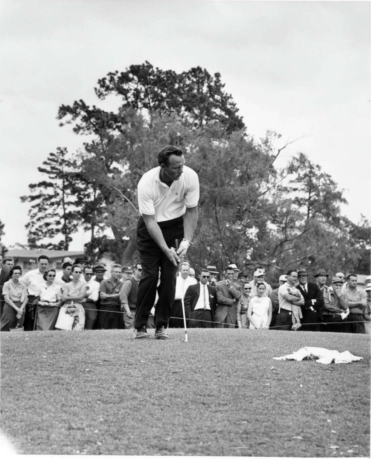 Golfing legend Arnold Palmer chips onto the ninth green of the Memorial Park golf course during the 1961 Houston Open. He won the event in 1957 and 1966.