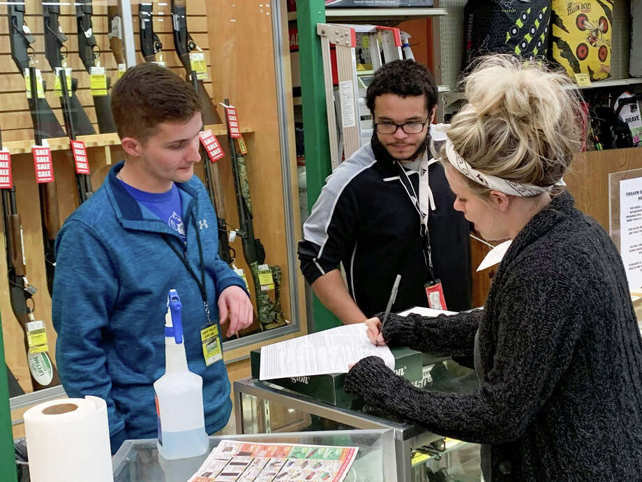 Dunham's Sports managers Ty Fulco and Miles Davenport help Morgan Sian purchase a gun on March 18, 2020. (Mitchell Kukulka/Mitchell.Kukulka@mdn.net) Photo: (Mitchell Kukulka/Mitchell.Kukulka@mdn.net)