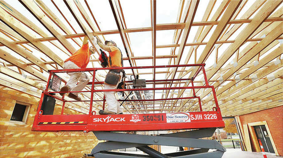 """Workers Thursday, from GRP/Wegman based in Bethalto, have nearly finished the framework for the new """"open space"""" area being built onto the Laux Brickhouse Grille, 212 N. Prairie St. in Bethalto."""