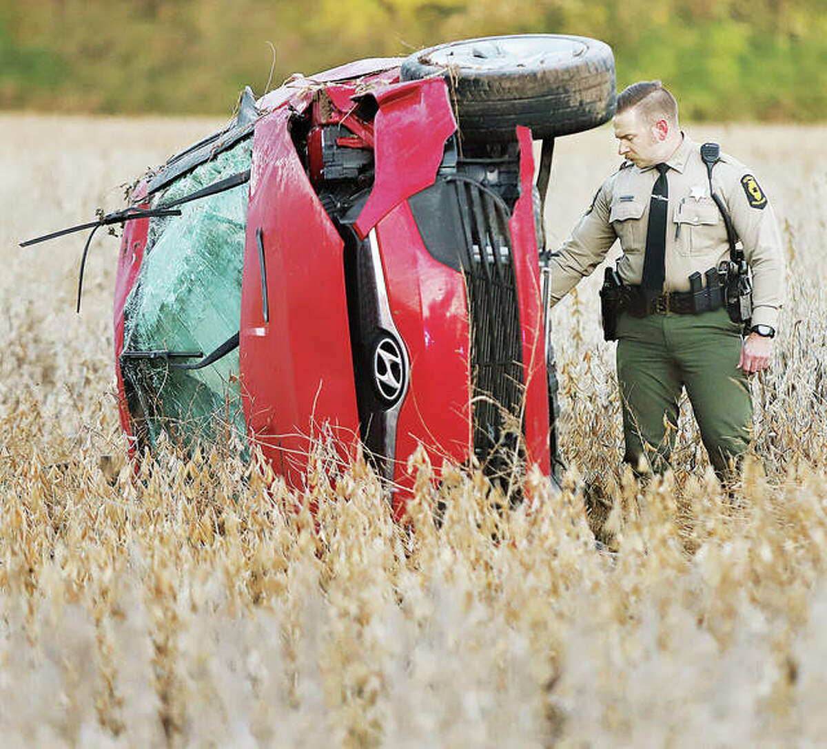 An Illinois State Police trooper examines the underside of a Hyundai as it lays on its side in a soybean field early Tuesday off Fosterburg Road, south of Emma Kaus Lane in Alton. A female was apparently ejected from the vehicle after it rolled over in a crash during the night and was not found until daybreak around 6:25 a.m. The woman's body was found laying in the field about 30 feet away.
