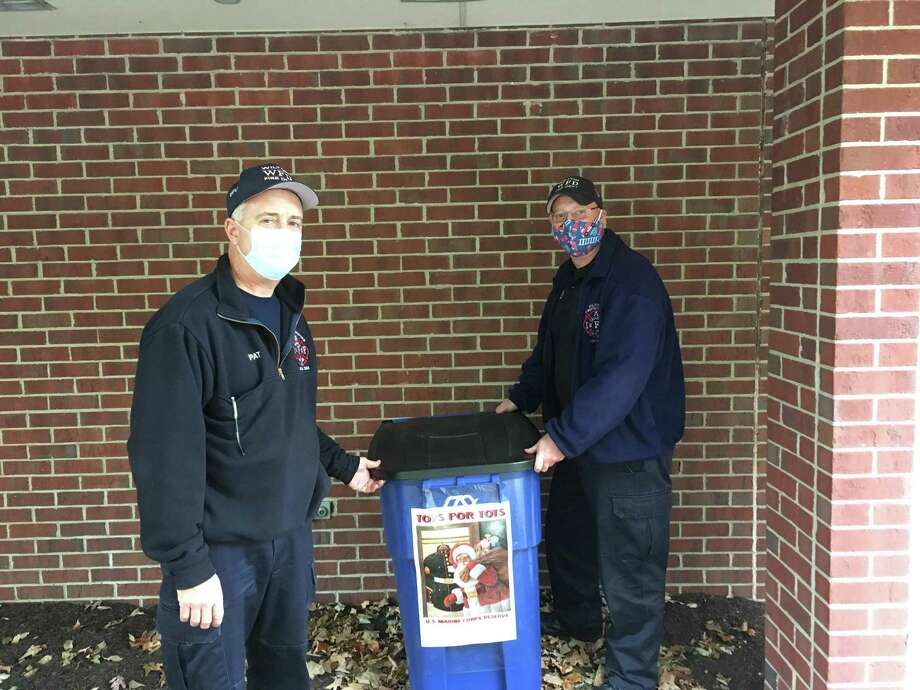 Firefighter Patrick Garber, left, and Capt. Brian Elliott stand by the blue bin designated for the drop-off of new, unwrapped toys for the Toys for Tots collection. The box is at fire headquarters at 236 Danbury Road. Photo: Wilton Fire Department / Contributed Photo / Wilton Bulletin Contributed