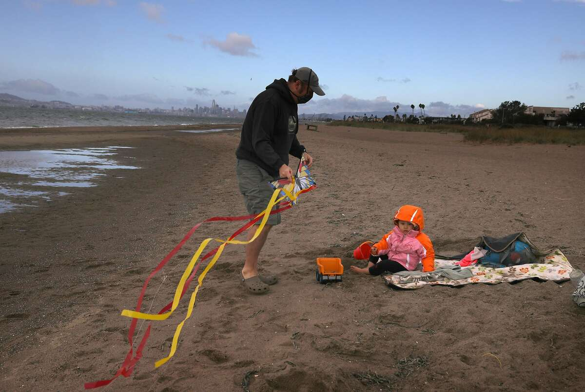 Jason O'Connell plays in the sand at Alameda Beach on Friday with his 2-year-old daughter, Maren.