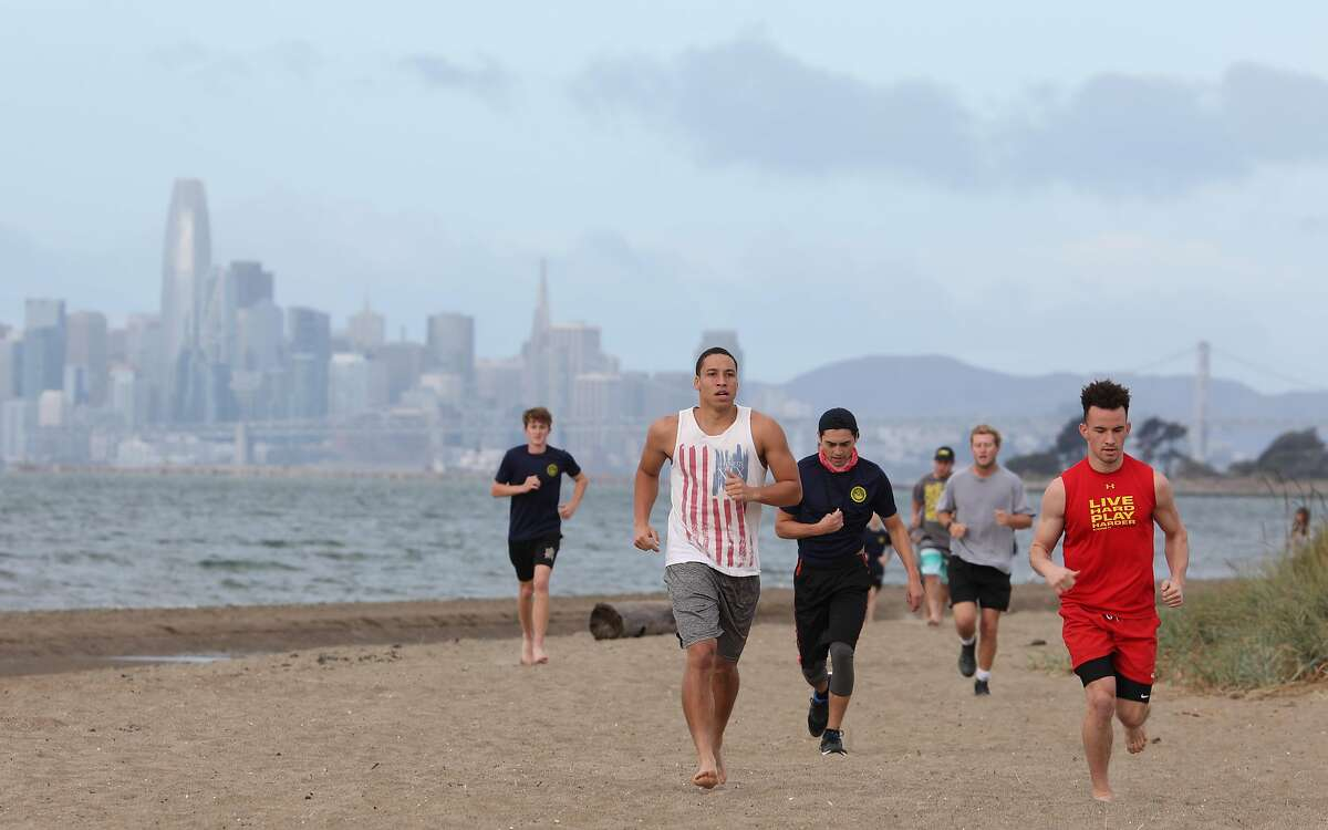 A group runs at Alameda Beach on Friday before expected scattered showers move in to the Bay Area.