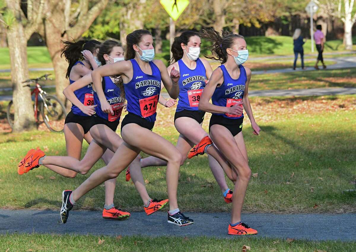 Saratoga's Ella Kurto, right, leads her team in a cross country meet against Shenendehowa at Saratoga Spa State Park. Saratoga score a perfect 15 points in seven of eight meets.