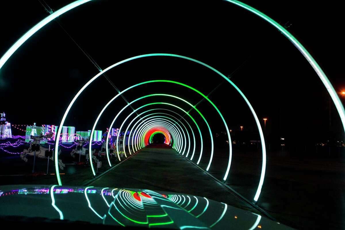 """The 700-foot long LED tunnel is one of the attractions at The Light Park, a new drive-through holiday experience are shown Monday, Nov. 2, 2020 in Spring. The attractions also include more than 1 million LED lights for a one-mile show that is synched and choreographed to holiday music on a dedicated station. """"Character DJs"""" including Santa, DJ Snowflake, Pixel Penguin and Barry Bear will work candy-cane turntables, adding to the cheer. Each pass-through ride will be different."""
