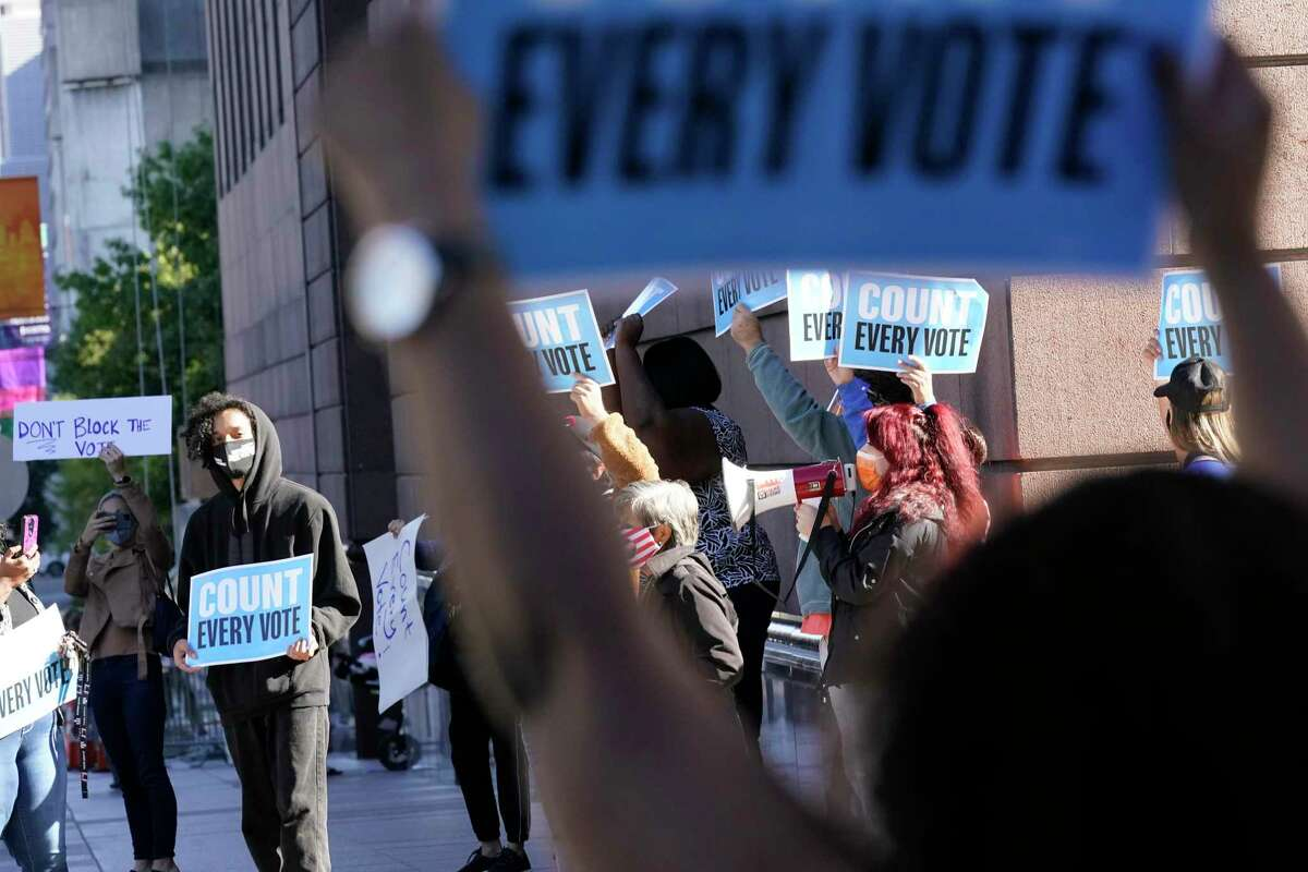 Demonstrators gather outside federal court in Houston on Monday to denounce a legal challenge to drive-thru ballots cast in Harris County.