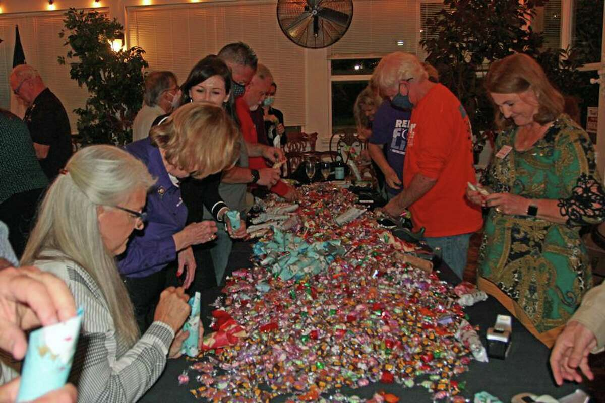 Mounds of candy being stuffed into tissue holders for holiday gifts for needy children in Mexico at the annual RC Lake Conroe Candy Roll Meeting.