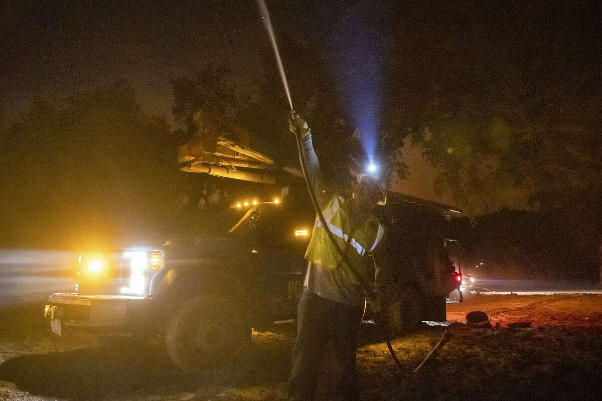 A PG&E employee sprays water on a burning telephone pole during the Zogg Fire in Shasta County in September.