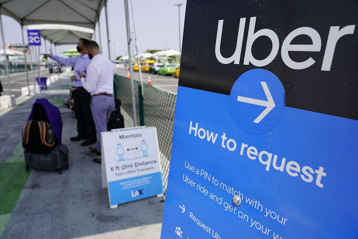 Travelers request an Uber ride at Los Angeles International Airport - Uber and Lyft drivers remain contractors under Proposition 22, but that could be changed by the federal government.