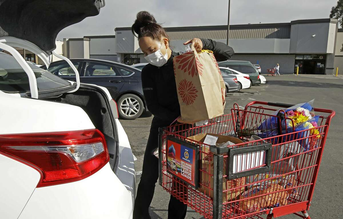 Instacart worker Saori Okawa loads groceries for delivery in San Leandro in July.