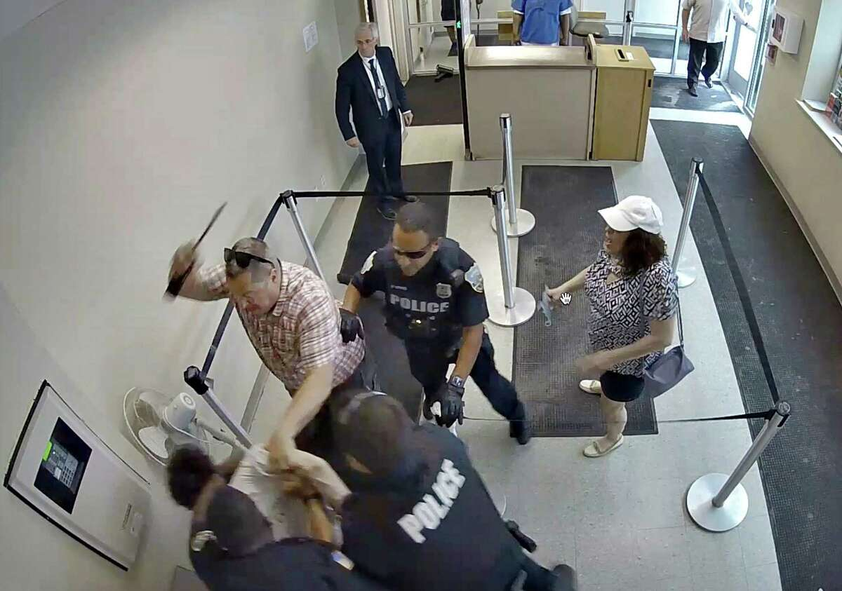 Frame grab from security camera footage shows Jason Daigneault of Schenectady being hit with radio by Schenectady law enforcement officers after he became frustrated after being asked to wear a mask before entering the Schenectady County Social Services building during a visit this summer with his mother, Cheryl, right.