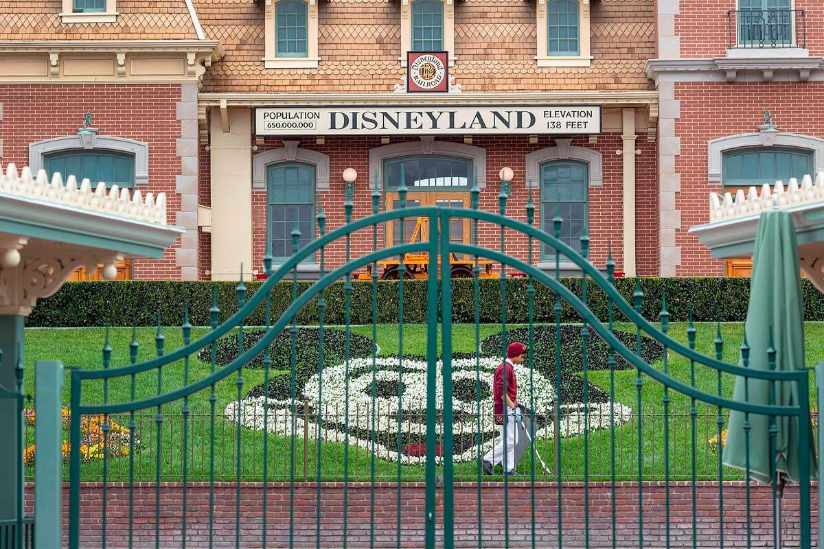 An employee cleans the grounds of Disneyland in March, its first day of closure due to the pandemic. Orange County officials are clamoring to reopen the park, but the state says no.