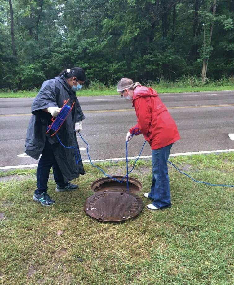 Researchers Becca Ives and Nishita D'Souza lower a container into a manhole to sample wastewater at Michigan State University. (Capital News Service photo)